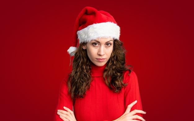 Mädchen mit dem weihnachtshut, der arme gekreuzt hält