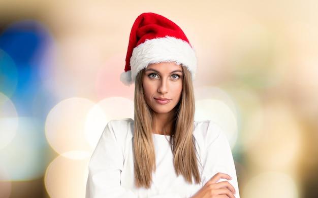 Mädchen mit dem weihnachtshut, der arme hält, kreuzte über unfocused hintergrund