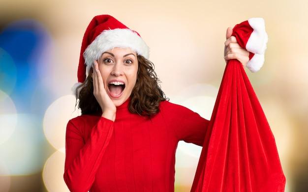 Mädchen mit dem weihnachtshut, der eine weihnachtstasche voll von den geschenken auf unfocused wand hält