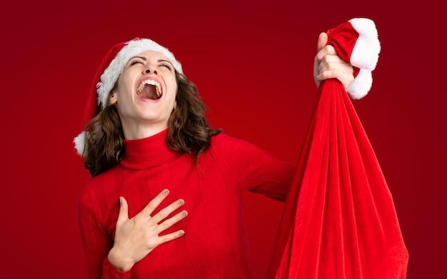 Mädchen mit dem weihnachtshut, der eine weihnachtstasche voll von den geschenken über lokalisierter roter wand hält