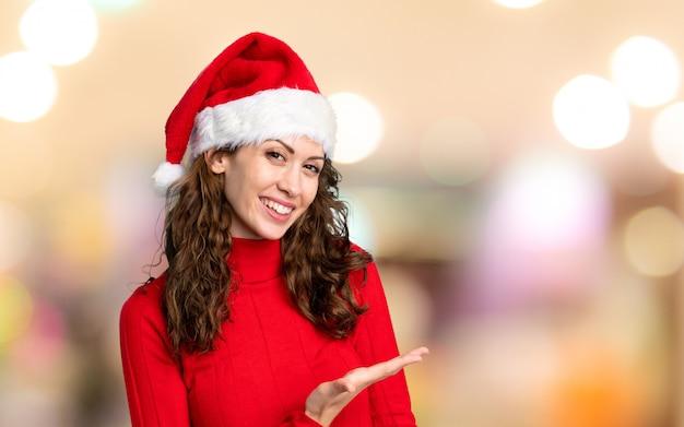 Mädchen mit dem weihnachtshut, der hände zur seite für die einladung verlängert, über unfocused hintergrund zu kommen