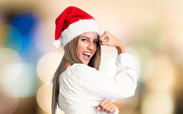 Mädchen mit dem weihnachtshut, der starke geste macht