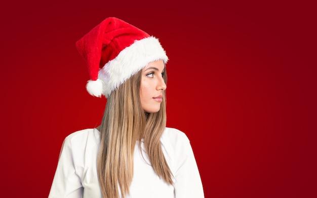 Mädchen mit dem weihnachtshut, der zur seite schaut