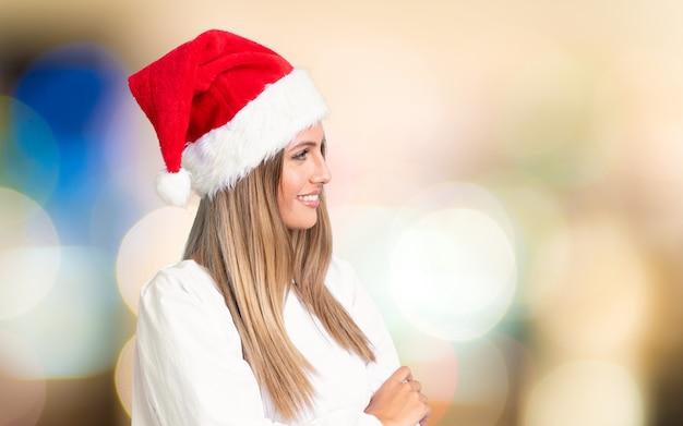 Mädchen mit dem weihnachtshut, der zur seite über unfocused wand schaut