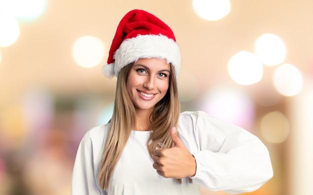 Mädchen mit dem weihnachtshutgeben daumen up geste über unfocused wand