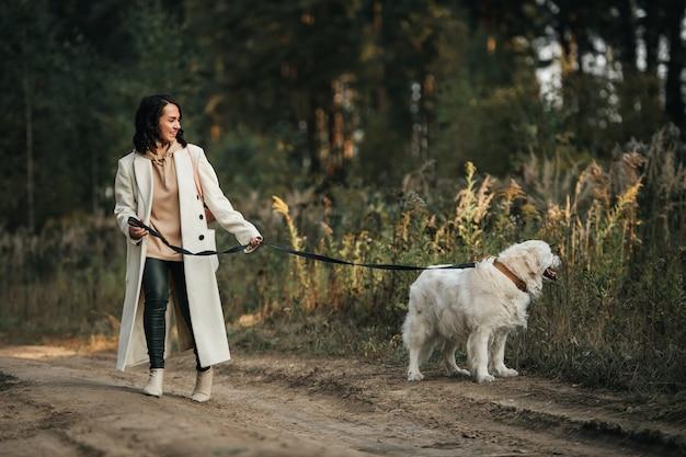 Mädchen mit dem weißen goldenen retrieverhund auf dem waldweg