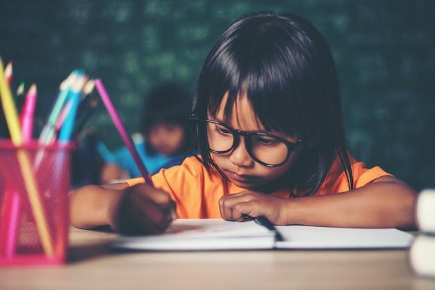 Mädchen mit dem zeichenstift, der am unterricht im klassenzimmer zeichnet