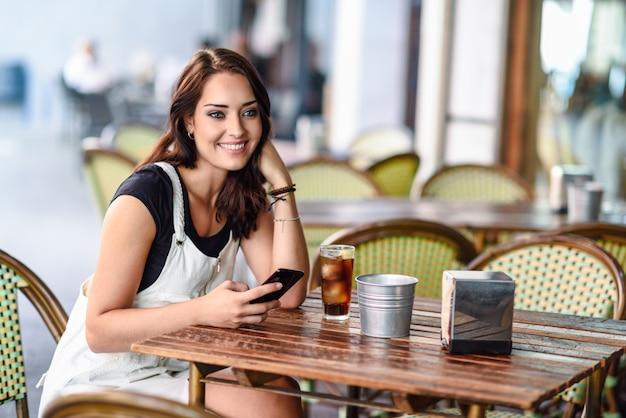 Mädchen mit den blauen augen, die auf städtischem café unter verwendung des intelligenten telefonlächelns sitzen