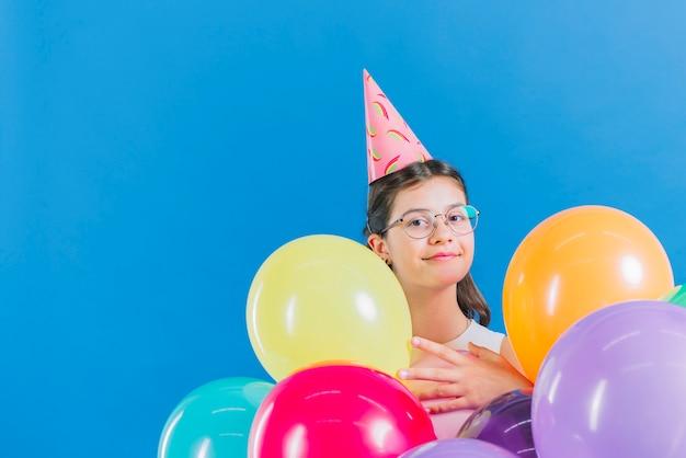 Mädchen mit den bunten ballonen, die kamera auf blauem hintergrund betrachten