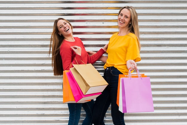 Mädchen mit den einkaufstaschen, die kamera betrachten