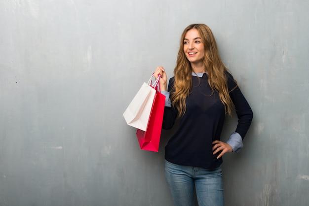 Mädchen mit den einkaufstaschen, die mit den armen an der hüfte und am lachen aufwerfen