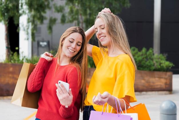 Mädchen mit den einkaufstaschen, die telefon betrachten