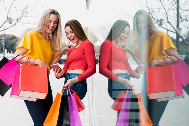 Mädchen mit den einkaufstaschen, die telefon nahe fenster betrachten