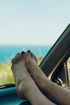 Mädchen mit den füßen aus dem fenster des autos, das an einem sommernachmittag ein sonnenbad nimmt,