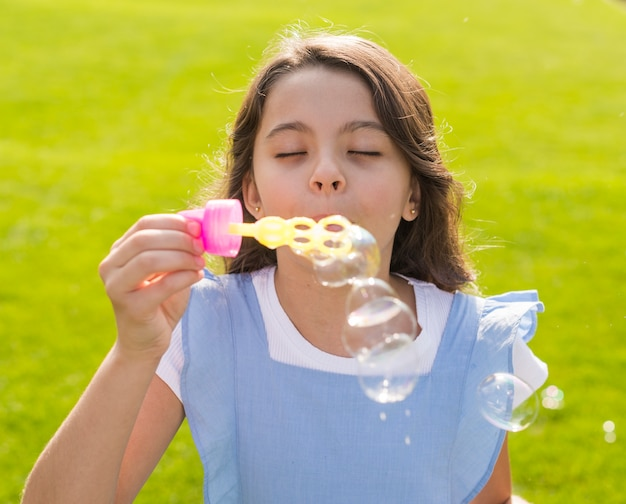 Mädchen mit den geschlossenen augen, die seifenblasen bilden