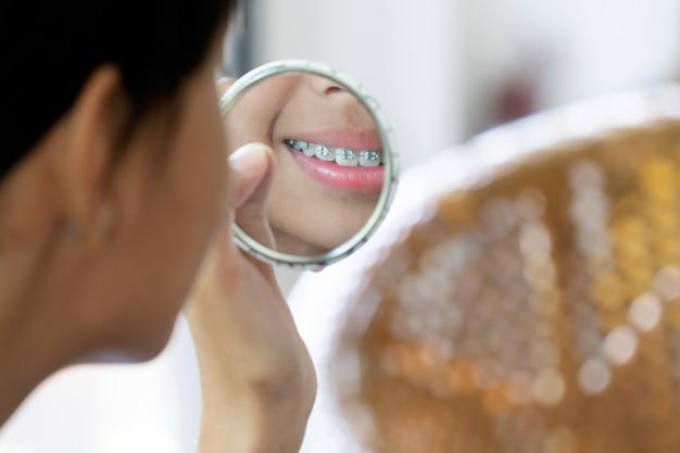 Mädchen mit den klammerzähnen, die zum spiegel säubert ihre zähne schauen