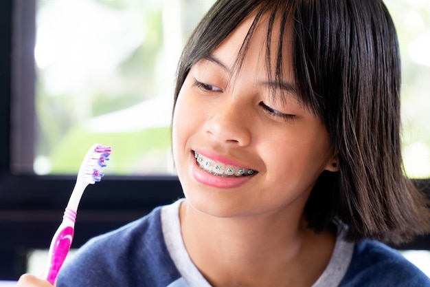 Mädchen mit den klammerzähnen lächelnd und glücklich
