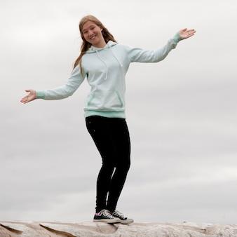 Mädchen mit den offenen armen, die auf felsen balancieren