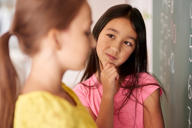 Mädchen mit der hand am kinn, das klassenkameraden betrachtet