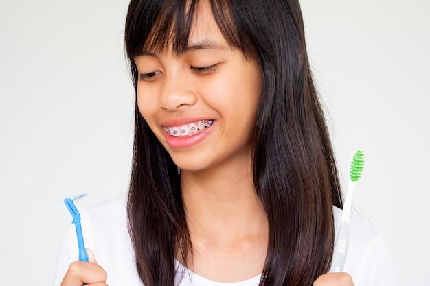 Mädchen mit der klammerzahnhand, welche die zahnbürste lächelt und glücklich hält