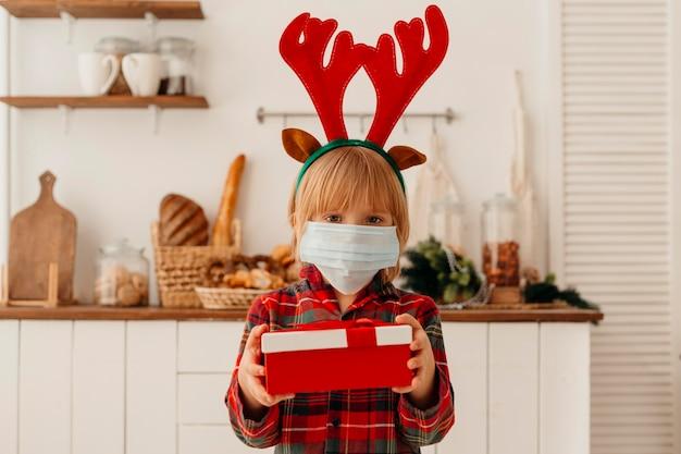 Mädchen mit der medizinischen maske, die ein weihnachtsgeschenk hält