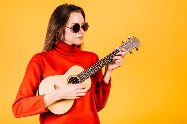 Mädchen mit der sonnenbrille, die das ukulele spielt