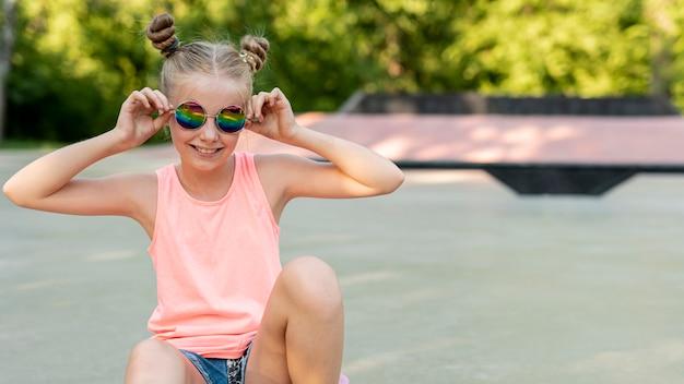 Mädchen mit der sonnenbrille, die im park sitzt