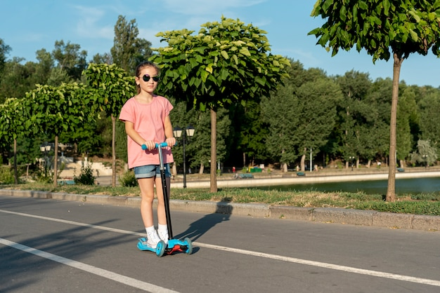 Mädchen mit der sonnenbrille, die roller reitet