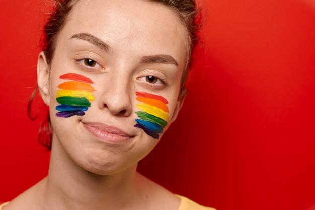Mädchen mit der stolzflagge gemalt auf ihrem backenlächeln