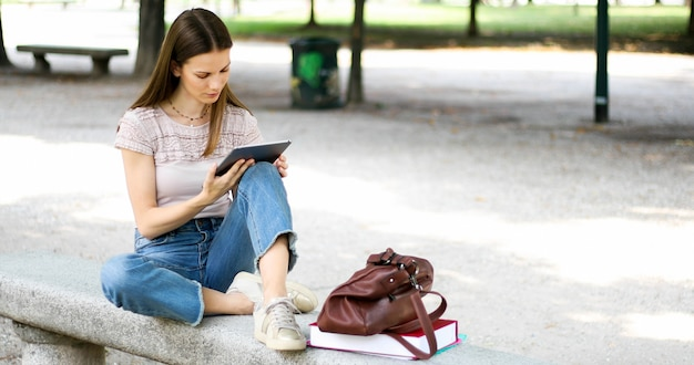 Mädchen mit der tablette, die auf einer parkbank sitzt