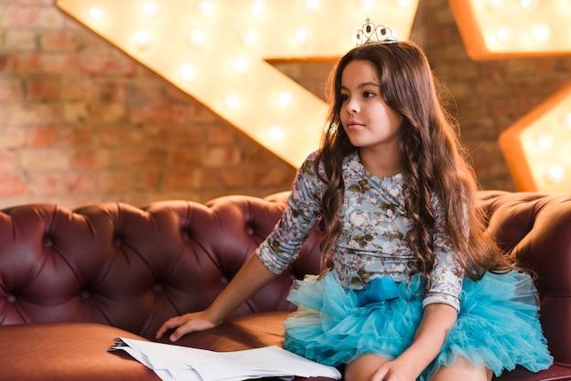 Mädchen mit der tragenden krone des langen haares, die auf sofa mit skripten sitzt