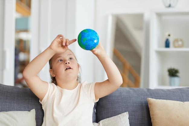 Mädchen mit down-syndrom, das modell des planeten in ihren händen beim sitzen auf sofa im wohnzimmer betrachtet