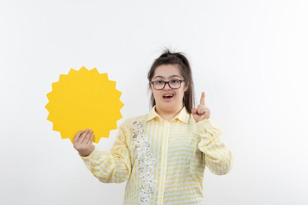 Mädchen mit down-syndrom in brillen, die mit leerer sprechblase stehen.