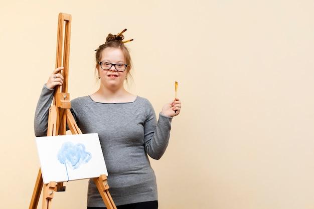 Mädchen mit down-syndrom posiert mit staffelei und kopierraum