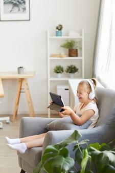 Mädchen mit down-syndrom sitzt auf sessel in kopfhörern und beobachtet etwas auf tablet-pc und lacht