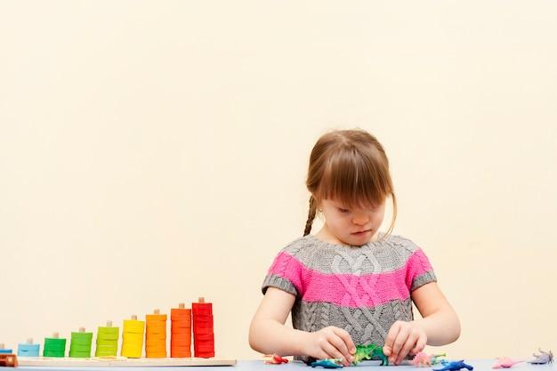 Mädchen mit down-syndrom spielt mit spielzeug