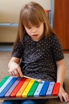 Mädchen mit down-syndrom spielt mit xylophon
