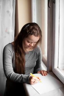 Mädchen mit down-syndrom zeichnung durch das fenster