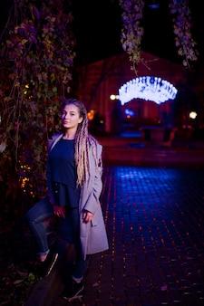 Mädchen mit dreadlocks gehend an der nachtstraße der stadt gegen girlandenlichter.