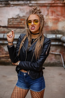 Mädchen mit dreadlocks, lederjacke, gelber brille, strumpfhose