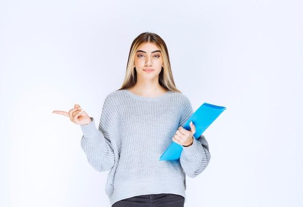 Mädchen mit einem blauen ordner, der beiseite auf jemanden zeigt.