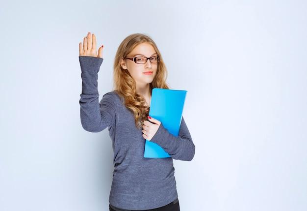 Mädchen mit einem blauen ordner, der ihre hand für aufmerksamkeit anhebt.