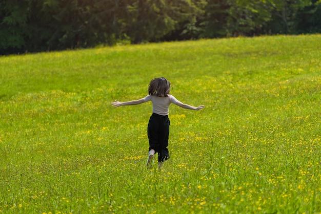 Mädchen mit einem blumenstrauß läuft auf der blumenwiese