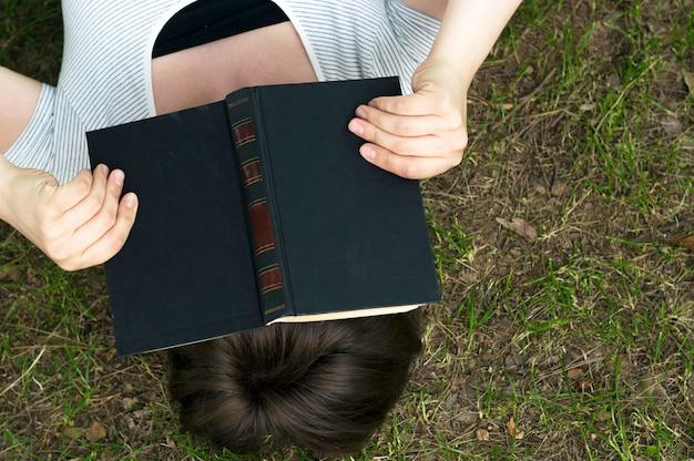 Mädchen mit einem buch liegt auf dem gras, draufsicht