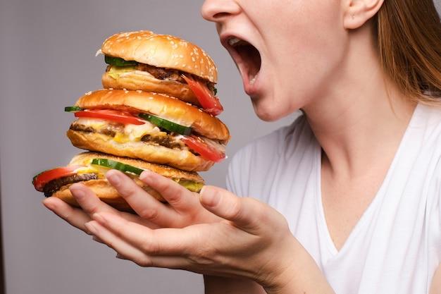 Mädchen mit einem burger in der hand öffnete ihre maus, um eine große portion hamburger zu essen