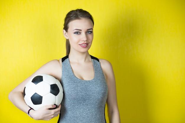 Mädchen mit einem fußball auf gelb.