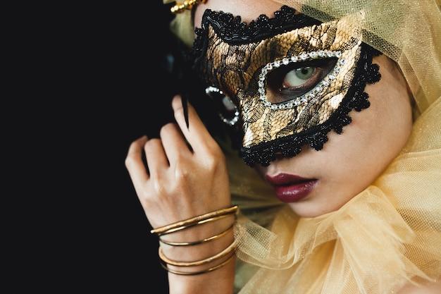 Mädchen mit einem gelben ornament auf dem kopf und eine venezianische maske