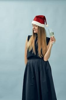 Mädchen mit einem glas champagner und einem weihnachtsmannhut