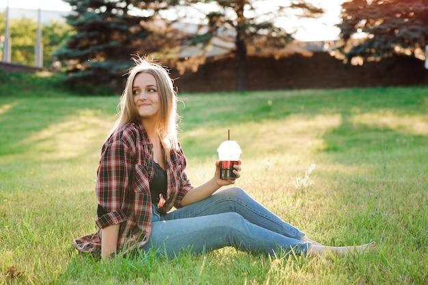 Mädchen mit einem glas saft auf einer grünen wiese.