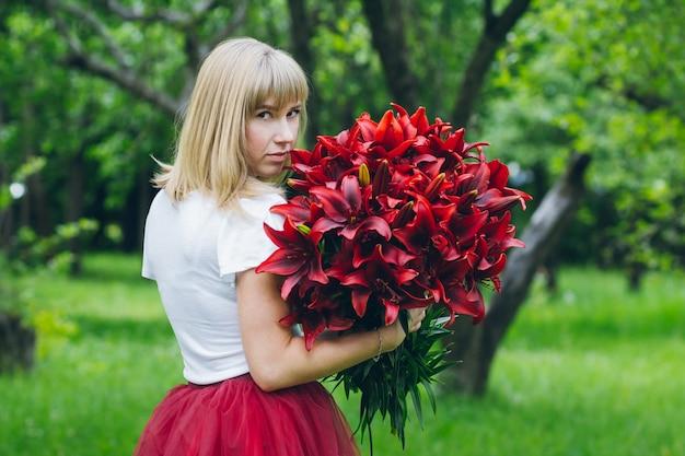 Mädchen mit einem großen strauß lila lilien